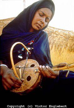 Niger. Sahara Desert. Tuareg nomad woman playing the anzad, a one-string violin..
