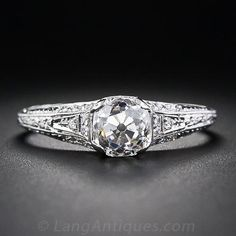 A gorgeous antique cushion-cut diamond, dating back to the first or second decade of the last century, and clocking in just two points shy of one-and-a-half carats, has found a splendid new home in a fully ornamented platinum and diamond engagement ring setting, recently crafted in faithful emulation of early-twentieth century Edwardian/early Art Deco style. The platinum mounting glistens on all sides with tiny full-cut diamonds and the ring shank is embossed all around with fine milgrai...