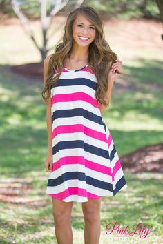 You'll feel like you're on a fantastic voyage while wearing this lovely dress! It flares out from the bust and has a comfortable racerback, which is perfect for warmer weather! Featuring navy, white, and hot pink stripes, this simple dress is also versatile enough for any occasion!