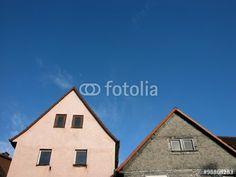Alte Wohnhäuser mit spitzem Giebel in Grau und Rosé vor blauem Himmel in Wißmar in Hessen