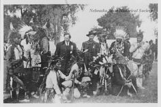 This is a posed group Santee Sioux Indians. They are with two white men, one wearing a suit and the other wearing a law-enforcement badge (identified as Captain B.J. Young). The Santee are dressed in traditional or ceremonial clothing, including feathers, breast plates and beads. Several hold pipes or other items. Date 1902/08/10