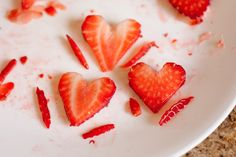 "Begin with one washed and dried strawberry Using a paring knife, cut off stem in a ""v"" shape, round tops of strawberry using knife. Slice strawberry in hal"