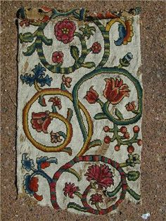 An English Elizabethan textile fragment complete loom width ca 1580.  Precursor to crewel work with embroidered white floss silk ground not woven silk.   Embroidery wool on jute backing. Note Elizabethan roses and Ottoman tulips found on Turkey work carpets of the period - CLICK TO ENLARGE