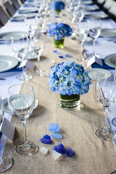 Small and low hydrangea centerpieces on top of a burlap linen runner at a rustic wedding reception.