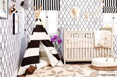 Grey patterned wall, cream baby crib, black and white striped teepee, cream printed rug, and animal decorations