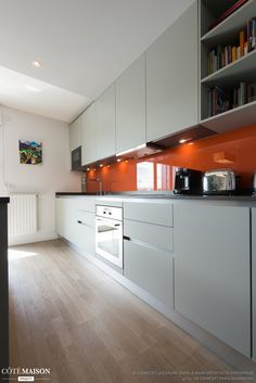 Une cuisine en longueur avec crédence en orange laquée.