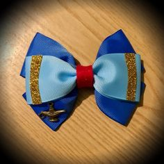 Genie Disney Character Inspired Aladdin Hair Bow Royal and Light Blue Grosgrain Ribbon Decorated with Gold glitter details, red glitter felt centre & mini lamp detail. 4 inch bow. Mounted on an alligator clip. I can do custom bows, just let me know if youd like something specific. Price is for single bow.