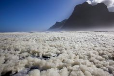 Sea Foam floats on the Atlantic Ocean, cliffs of Sentinel Mountain in Hout Bay, Cape Town, South Africa. Sea foam created by churning of the seas before a southern ocean storm. Ocean Storm, Ocean Day, Pictures Of The Week, Cool Pictures, Oceans Of The World, Out Of Africa, Africa Travel, Continents, Science Nature