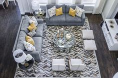 EJ Interiors - living rooms - Wisteria chairs, x benches, herringbone cowhide rug, wood floors, glass coffee table, fabricut pillows, yellow accents, Global Views end tables with black granite tops, gray and yellow living room,