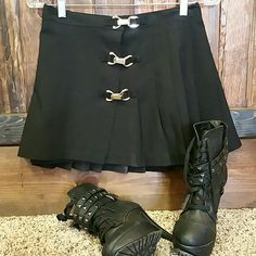 Pleated Black Mini Skirt PRE OWNED. Vintage.  Cute! Cute! Cute! Black Mini skirt features a pleated back, a half pleated front, 3 silver buckles, and buttons on the inside with 2 buttons. One of which is missing. If you can sew one on, you're golden! Good condition. Rave Skirts Mini