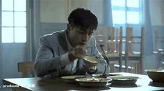 A Chinese guy demonstrates how to eat veggies with a pair of chopsticks.