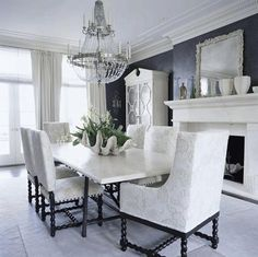 Silver crystal chandelier, silk white drapes, crown molding, white black dining table, upholstered white ivory and black dining chairs, limestone fireplace, mirror, white hutch, and black walls.