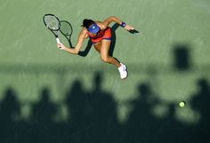 Ana Ivanovic of Serbia hits a return to Alexandra Dulgheru of Romania as the shadows of spectators show on the court at the U.S. Open tennis championships in New York August 29, 2013. REUTERS/Eduardo Munoz