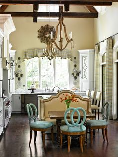 """A banquette covered in """"pleather"""" backs the island of this Atlanta kitchen. Side chairs designed by Barry Dixon are covered in Ultrasuede, a surprisingly easy-to-care-for fabric - Traditional Home®"""