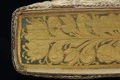 Embroidered cloth binding: Edge with painting and gauffering  Photo: István Borbás/National Library of Sweden   This beautiful binding is among the best preserved and most splendid of its kind. The floral motifs are embroidered with satin stitching in silver and luminous colours. The edges are lavishly decorated, painted in gold and other colours and with gauffering. The front edge shows the symbol of hope, a woman with an anchor.