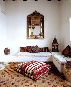 Moroccan room filled with texture: embroidered raffia rugs, wedding blanket upholstery, flat weave cushions, Moroccan lanterns.