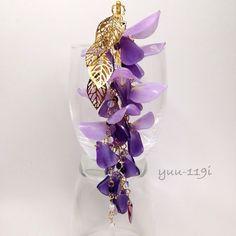 藤の花(ふじのはな)の簪になります花のお色は薄紫と紫中央はイエロー。シンセティックオパールを使用シンセティックオパールとカットされた紫のチェコビーズをチェーンのように繋げております花の1番下にチェコビーズ(ダガー)のホワイト(フロスト)を一つ、紫を二つ7枚のゴールドの葉を使用浴衣や着物にも。かんざしの長さ 12.5cm藤(大) 約3.8×1.8cm藤(小) 約1.8×1.4cm葉 約2.4×1.4cm飾り部分 約15cm葉の全長 約5.5cmチェコビーズ(紫) 4mmシンセティックオパール 4mmチェコビーズ(ダガー) 16×5mm素材はプラバンですこちらの商品は着色後にニス止めとレジンで加工しております。とても繊細な商品ですので気をつけてお取り扱いください箱に入れての発送となります。一つ一つ丁寧に作っておりますがハンドメイドの為若干の色の濃さ、形が違います神経質な方はご遠慮ください『春ハンドメイド2017』