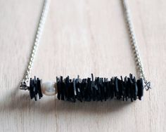 Upcycled bicycle inner tube horizontal bar necklace with a single large freshwater pearl.