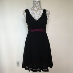 AE Black Dress  American Eagle black dress with removable purple sash around waist. Size 0. Good condition, no flaws. Has a small hidden side zipper. Shell: 100% polyester. Lining: 100% polyester. Skirt part of the dress has two layers. Hits at the knee. American Eagle Outfitters Dresses Midi