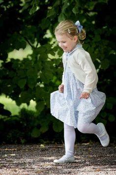 Prinsessan Estelle var klädd i en blå sommarklänning med krage när hon firade mamma Victoria på Solliden. Lillsessan var redo för regn, med ett blått paraply i höga hugg. När det sedan började regna var ingen mer förberedd än Estelle.