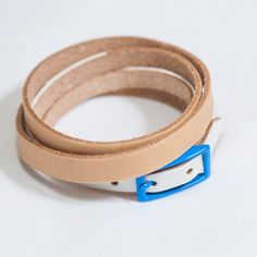 White and Tan Skinny Strap-- Belt or Wrist band? You decide, Kids. Love the neon blue accent buckle. $49
