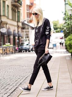 Ellen Claesson wearing a black graphic sweater, black cropped trousers, and black converse