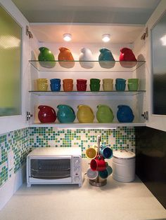 Love the clear cabinets and colorful dishes.