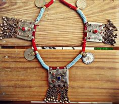 This beautiful vintage necklace is made of many ethnic finds- The main necklace is comprised of vintage afghan Amulet pendants also known as Taweez in the local language.The main pendant is heavily carved with geometric carvings.  Adorned with Afghan glass stones and metal tussles.  When worn,it hangs at around 22 inches.Perfect statement piece and light weight.  Button closure at the back for secure wear.
