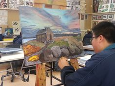 Jun Lee at the easel, finishing off his work.