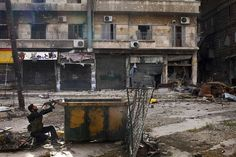 A Syrian rebel takes position behind a makeshift barricade during clashes with regime forces in the Salaheddine district of Aleppo, on March 16, 2013. (JM Lopez/AFP/Getty Images
