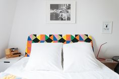 A white and bright minimal space doesn't have to be boring. Check out this bold headboard full of color and geometric patterns!