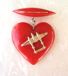 *VINTAGE BAKELITE PUFFED RED HEART:Dangle Sweetheart Brooch Pin WWII from atwinkleintime:this fantastic Bakelite Brooch features an applied WWII gold metal 3-demensional Lockeed P-38 Fighter Bomber Airplane placed over the Puffed heart. This plane was one of the most recognized U.S. Aircraft of WWII because of it's unusual design. The Heart is vibrant red and carved at the top.