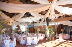 Wedding reception complete with drapes, chandeliers, and beautiful linens!