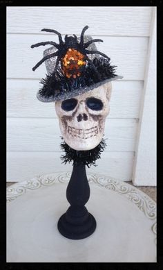 James Goodwin is a dapper skull wearing a silver glittered top hat. His hat sports a dashing glittered spider. Skull is sitting on a black candlestick.