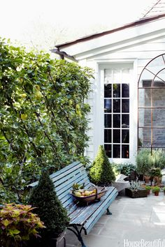 The house merges indoors with outdoors. On her front terrace, antiques dealer Jeannette Whitson designed a Charleston-inspired secret garden enclosed by pear trees espaliered on a trellis. An arched window adds architectural interest.   - HouseBeautiful.com
