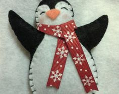 Christmas DIY: This item is a handm This item is a handmade felt penguin Christmas ornament. It is designed and handmade by me! I make him with either a red blue or striped Felt Christmas Decorations, Christmas Ornaments To Make, Christmas Sewing, Noel Christmas, Xmas Crafts, Christmas Projects, Handmade Christmas, Felt Projects, Christmas Felt Crafts