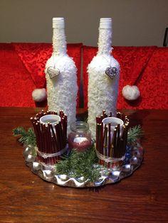Potjes met takken beplakt en wijnflessen met sneeuw beplakt. Beetje groen erbij en klaar is het kerststukje.