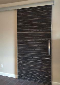 Contemporary modern barn door with Bella Laminati Zebrano walnut wood veneer.