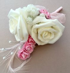 Winter white artificial wedding corsage with silver pearled spray, pastel pink mini roses and a feather. finished off with pastel pink satin bound stem and bow..
