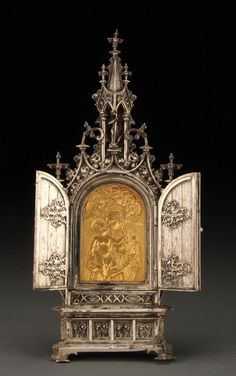SILVERED AND GILT GOTHIC TRIPTYCH, 19TH CENTURY, PROBABLY VIENNESE.  The central arched reserve set with a gilded plaque of the Virgin and Child sculpted in high relief with fine detailing and with heavenly cheribum at top on a stippled ground. Behind the hinged doors within twist column flanked niches, figures of St. George (left) and St. Florian (right). Above the ornate top spire within a niche with overhanging canopy, a sculpted figure of the Archangel Michael defeating Satan.