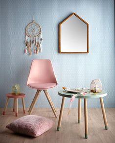 Accessoires au style ethnique avec un petit coussin en fourrure rose, chaise, table ronde et déco murale