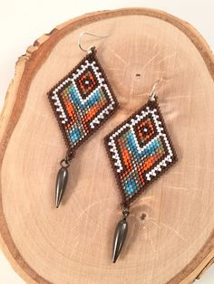 Handmade diamond shaped beaded earrings with intricate tribal design. Eight colors merged with steel finished hex cut beads in an…