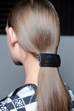 New Ways To Wear Pins, Barrettes, & More: The Leather Barrette - Bored with the classic ponytail? By adding an edgy leather barrette to this classic style, you can instantly take your preppy pony from boring to bangin'. Keep your hair low to the nape of your neck for a classic look, or pull half of it up for a new twist on the, um, twist.