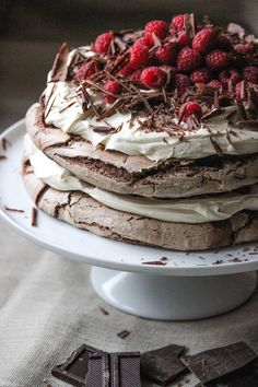 A rich chocolate meringue layer cake. Chocolate meringue, layered with vanilla bean whipped cream, topped with raspberries and chocolate shavings.