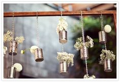 Could do white hydrangea and baby's breath in tin cans hanging down from twine.  Wrap the cans in twine.  Could also cut these down after the ceremony and reuse on reception tables (save costs).