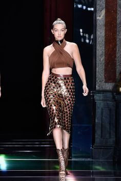 Gigi walked the Balmain runway in a bronzed look, baring her midriff in a halter neck crop top and matching her golden skirt to a statement choker.