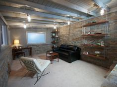Stone walls add texture to the space while the exposed ceiling joists provide a touch of industrial style. The shelves are suspended from the ceiling with galvanized chains, and a stand-up bar in the corner is perfect for entertaining guests.