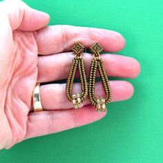 Bronze Beaded Herringbone Earrings Bronze Gold Dangle Earrings Bronze Post Earrings Bronze Loop Earrings This contemporary pair of earrings was hand-beaded using large three different sizes of bronze seed beads in a herringbone pattern. I then suspended little embellished crystal wheels in a tapered area on the beaded loops and finished them with post earring blanks that I also beaded using tiny bronze seed beads to match the earrings. The little crystal wheels are free to turn on the…
