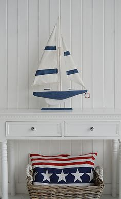 New England style accessories. Cushion, basket and decorative wooden boat in white and navy from the White Lighthouse