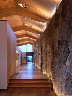 Faceted wood ceiling in hallway with natural stone wall including cove lighting and clerestory window that accentuates the irregular shape of the ceiling